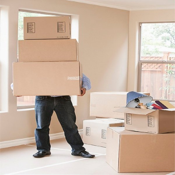 Hispanic man with cardboard boxes in new home